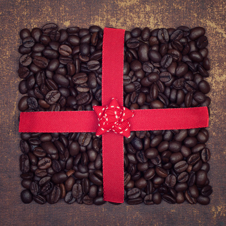 coffeebeans: The shape of a present made out of roasted coffee beans  on shabby chic surface Stock Photo
