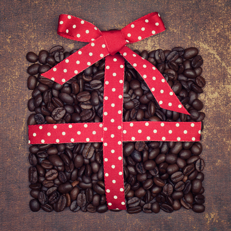 dot surface: The shape of a christmas present made out of roasted coffee beans  with polka dot ribbon on shabby chic surface