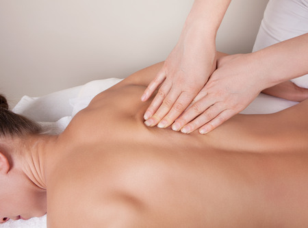muscle women: Connective tissue massage on  a muscle group (erector spinae muscles) of a womans back Stock Photo