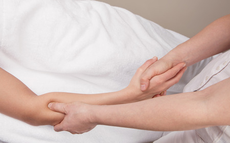 connective: Therapist doing a  deep tissue massage on of a womans right forearm Stock Photo