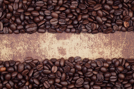 faux: Dark roasted coffee beans arranged in a frame on a grunge faux leather material surface