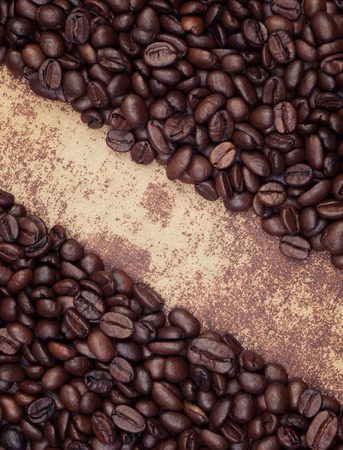 arranged: Dark roasted coffee beans arranged in a frame on shabby chic surface Stock Photo