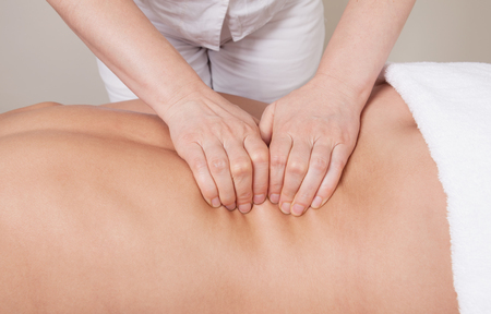 erector: Sport professional massage on a muscle group (erector spinae muscles) of a womans back Stock Photo