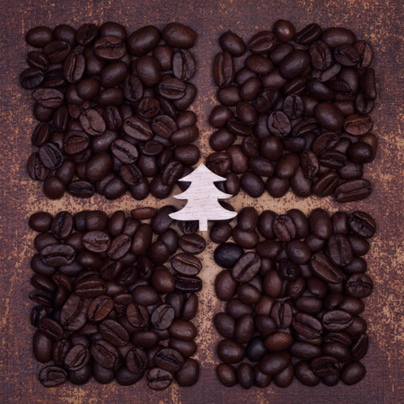 faux: Wooden christmas tree on dark roasted coffee beans divided into quarters on a faux leather material background