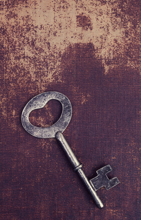 faux: Old vintage key on a faux leather material surface Stock Photo