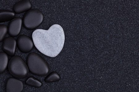 Black stones with grey zen heart shaped rock on  grain sand Stockfoto