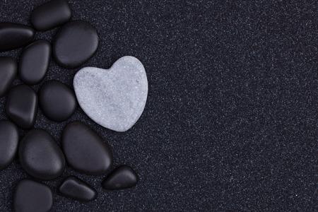 Zwarte stenen met grijze zen hart gevormde rots op korrel zand Stockfoto