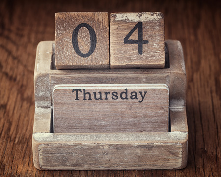 the thursday: Grunge calendar showing Thursday the fourth on wood background