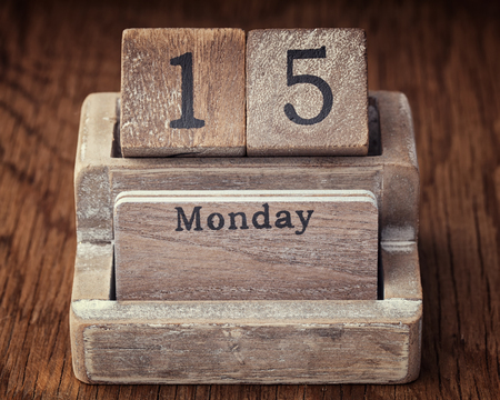 fifteen year old: Grunge calendar showing Monday the fifteenth on wood background