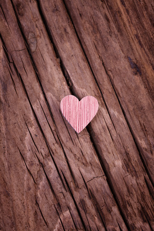wood craft: One pink wooden valentines heart  on an old  rustic wood