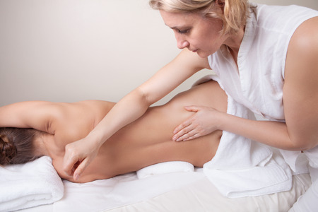 Professional massage. A therapist stretching clients oblique muscle, working with her forearm.