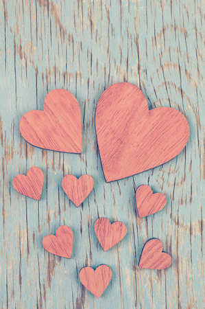 wood craft: Many pink wooden hearts placed  on an aquafresh color  vintage wood