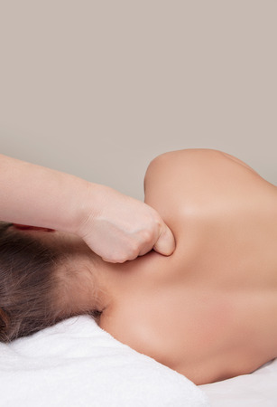 treating: Professional massage. Releasing tension in neck and shoulders. Working on upper trapezium. Stock Photo