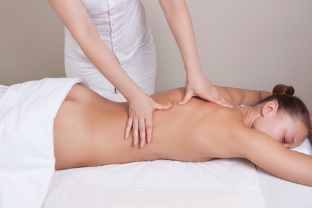 Deep tissue massage on the womans middle back