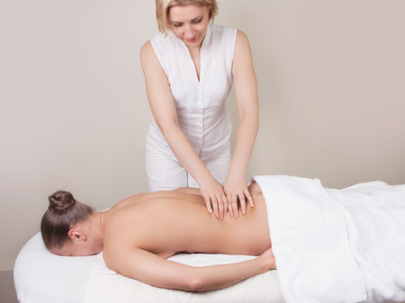 erector: Professional massage on a muscle group (erector spinae muscles) of a womans back
