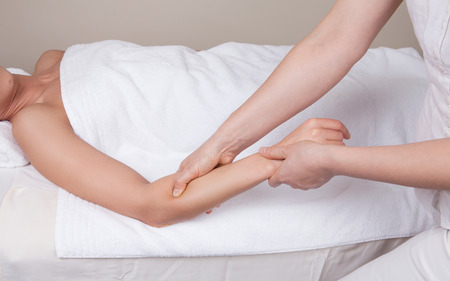 remedial: Professional  therapist doing  remedial deep tissue massage on muscles of a womans  forearm