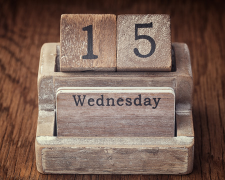 fifteen year old: Grunge calendar showing Wednesday the fifteenth on wood background Stock Photo