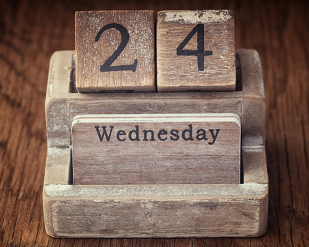 wednesday: Grunge calendar showing Wednesday the twenty fourth  on wood background