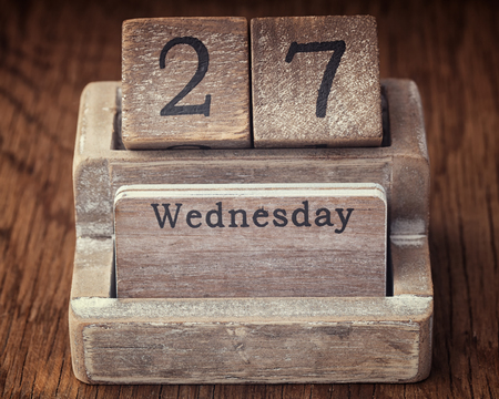 27 years old: Grunge calendar showing Wednesday the twenty seventh on wood background