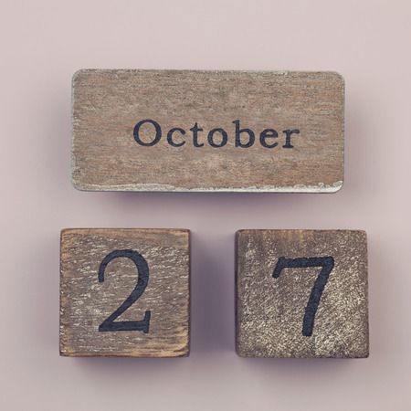 27 years old: Wooden vintage calendar showing the date 27th of October Stock Photo