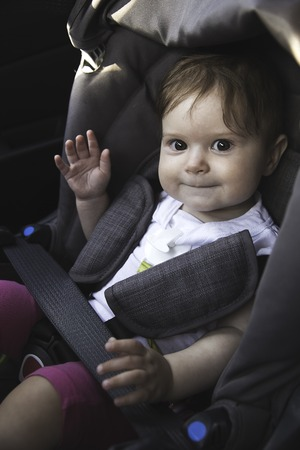 Cute little baby sits fastened in a car seat ready for a ride. Baby safety on the road concept