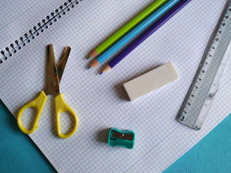 Back to school concept. Top horizontal view of school supplies on blue background. Color pencils, scissors, sharpener, eraser, ruler and notebook. Banque d'images