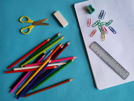 Back to school concept. Top view of school supplies on blue background. Color pencils, scissors, sharpener, clips, eraser, ruler and notebook. Banque d'images
