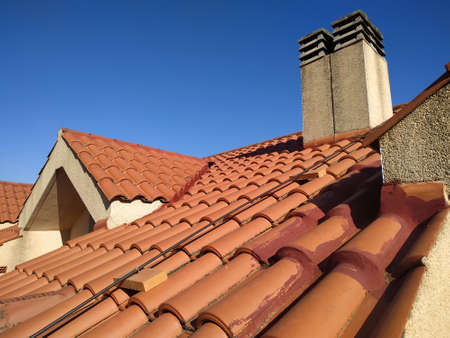 Tiles and chimney on the roof of a residential building attic over blue sky