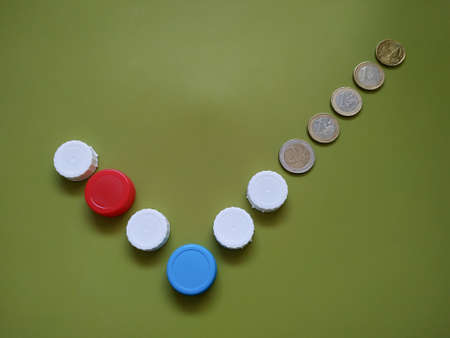 Plastic recycling concept generating finance profit. Caps and coins in the form of a check mark icon on green background. Фото со стока