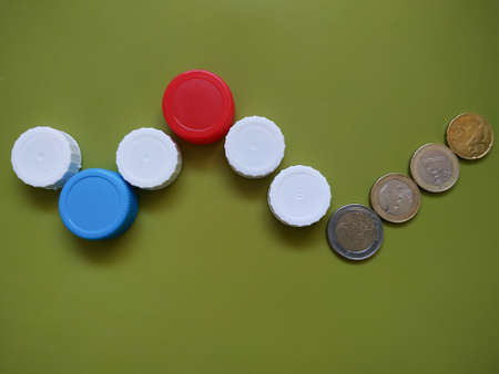 Plastic recycling concept generating finance profit. Caps and coins on green background.