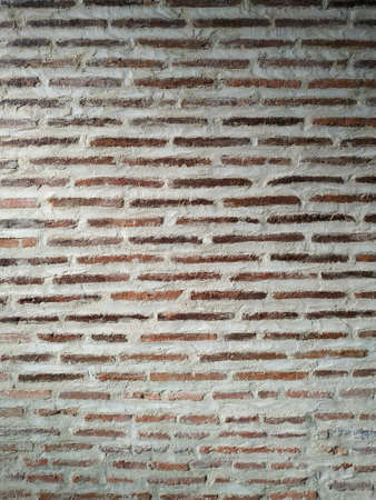 Old brick wall texture background. Front vertical view of masonry wall made of red bricks and white lime mortar Banco de Imagens