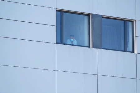 Coruña-Spain. Sick man looking through the hospital window with a mask on his face from the covid-19 coronavirus on March 26, 2020.