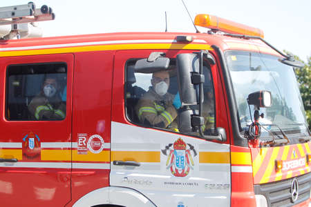 A Coruna-Spain.Firefighters with masks inside fire trucks during a tribute to the emergency services working during the coronavirus pandemic that affects Spain on March 26,2020
