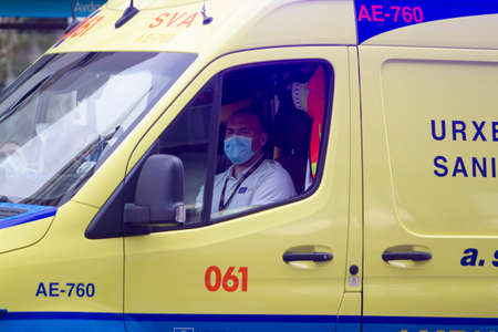 Coruña-Spain.Ambulance driver with face mask inside the vehicle on May 10,2020 Editorial