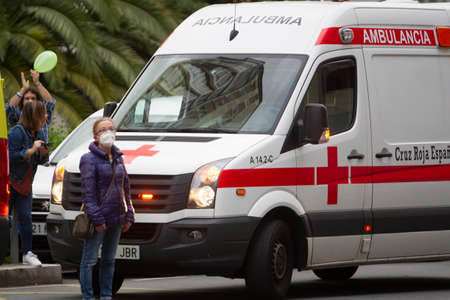 Coruña-Spain. Lady with mask next to ambulance of the red cross on May 10,2020