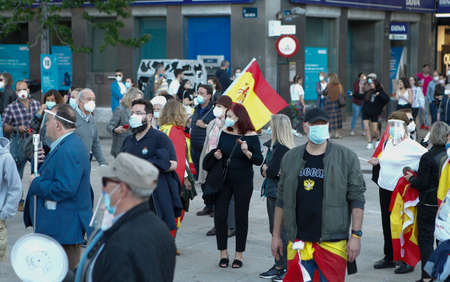 Coruña-Spain.Spanish protesters with face mask protesting touching a saucepan against the Spanish government's management during the covid-19 pandemic May 19, 2020