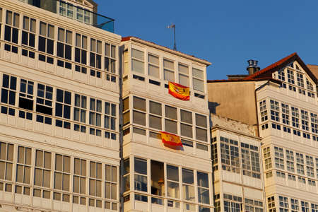 white wooden windows with flags of Spain with black clips in honor of those who died from the covid-19 pandemic in Spain