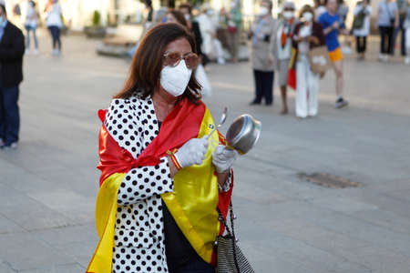 Coruña-Spain.Spanish protester with face mask protesting touching a saucepan against the management of the government of Spain during the covid-19 pandemic May 19, 2020 Editorial