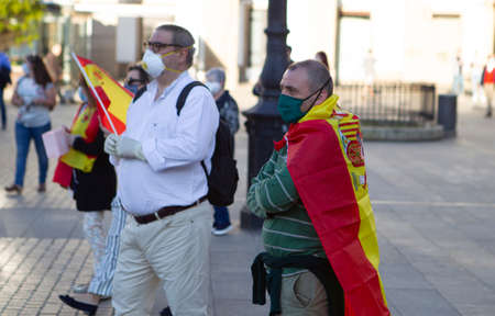 Coruña-Spain.Spanish protesters with face mask protesting touching a saucepan against the Spanish government's management during the covid-19 pandemic May 19, 2020 Editorial