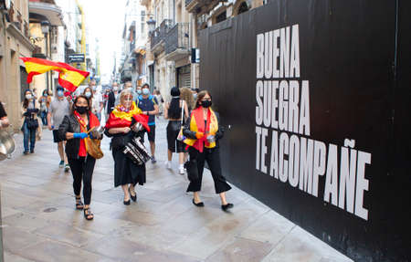 Coruña-Spain.Protesters with a mask protesting against the management of the government of Spain during the covid-19 pandemic pass by a wall that says good mother-in-law accompany you on May 20, 2020 Editorial