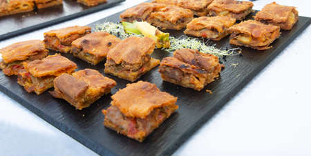 Pieces of Galician pie on slate tray with white background