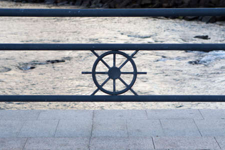 metal railing with rudder in the center at the edge of the sea