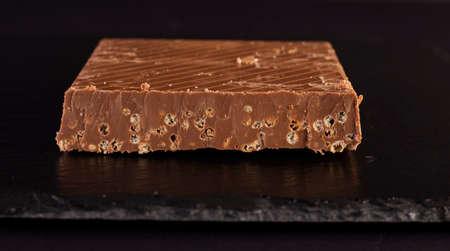 Piece of chocolate nougat on slate plate Foto de archivo