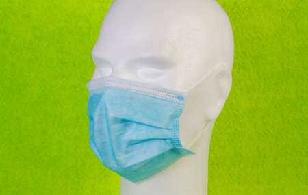White bust with a blue hygienic mask on a green background