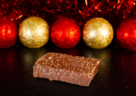 Piece of chocolate nougat on slate plate surrounded by christmas decoration