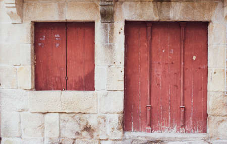 red painted wooden door on stone frame in medieval village Foto de archivo