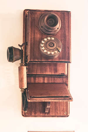 old wooden phone on white wall Editorial