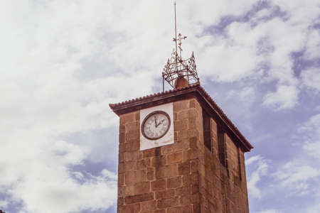 Clock tower of the church of Santiago with clouds in the background in Allariz, Ourense, Spain