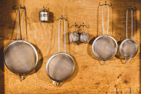 set of metal mesh strainers hanging on wooden background