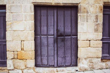 violet painted wooden door on stone frame in medieval village